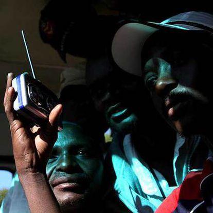 Un grupo de zimbabuenses escucha la radio en Harare a la espera de noticias sobre el resultado electoral.