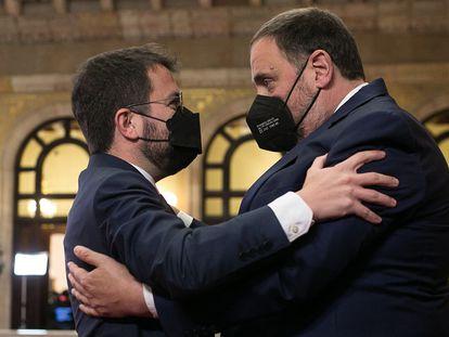 El nuevo presidente de la Generalitat, Pere Aragonès (a la izquierda), abraza al presidente de ERC, Oriol Junqueras, tras ser elegido por mayoría absoluta, este viernes.