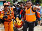 Rescue workers carry a body bag containing the remains of a victim of the tsunami in Pandeglang