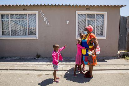 Elda Sidlabane (66) es recibida por Yamihla Lambatha (6) y Achumile Lambatha (10), sus nuevos nietos adoptivos, cuando llega a casa de su reunión de grupo de personas mayores en su vecindario del municipio de Khayalitsha, fuera de Ciudad del Cabo, Sudáfrica, el 19 de febrero de 2021.