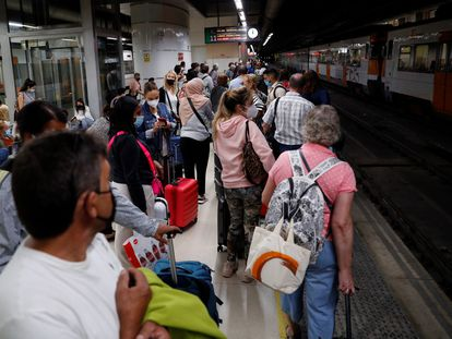 Decenas de pasajeros esperan en la estación de Sants en Barcelona la llegada de algún tren.