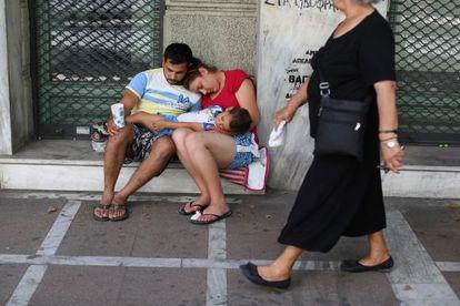 Una familia pide limosna a la puerta de un comercio cerrado en Atenas.