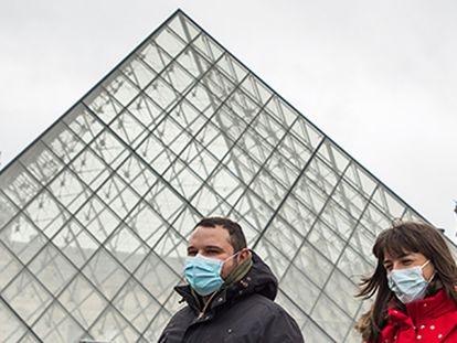 Dos personas con mascarillas pasan frente al Museo del Louvre de París.