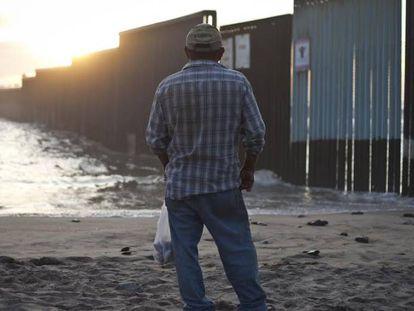 Un hombre contempla el muro en la playa de Tijuana