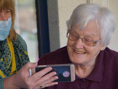 Una vecina ayuda a una anciana a hacer una videollamada.