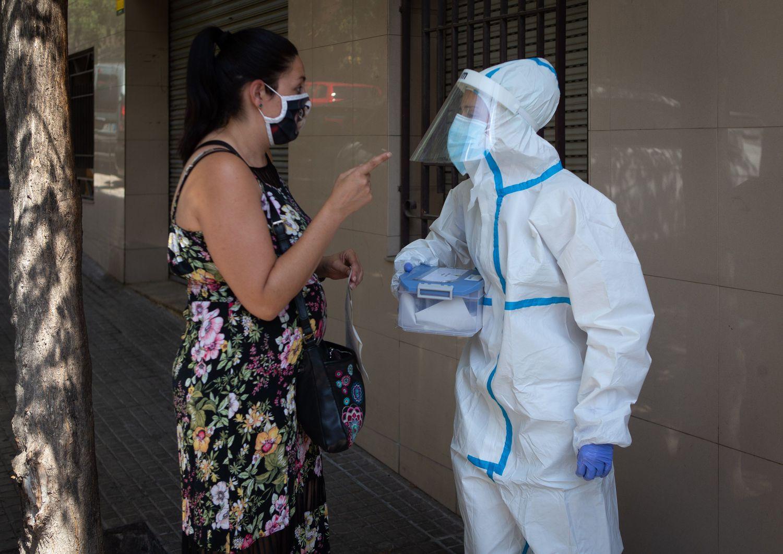 Una mujer habla con una sanitaria en Ripollet (Barcelona), donde la Generalitat comenzó este miércoles un cribado masivo y voluntario para detectar positivos.