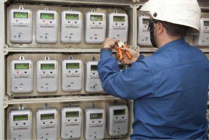 Un técnico instala varios contadores eléctricos.