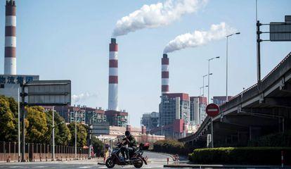 Un motociclista pasa frente a las chimeneas humeantes de una central de generación eléctrica en Shaghái (China).