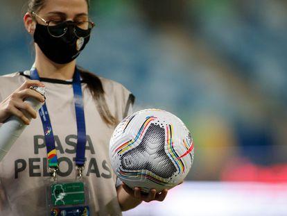 Una trabajadora de la Conmebol desinfecta un balón durante un partido entre Chile y Bolivia, en Cuiabá, en la Copa América.