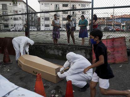 Empleados de una funeraria recogen en una favela de Río de Janeiro el cadáver de un hombre que, según los vecinos, tardaron 30 horas en retirar.