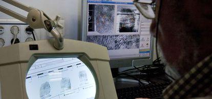 Un guardia trabaja con el programa de identificación de huellas dactilares.