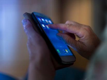 Un hombre usa un teléfono móvil.