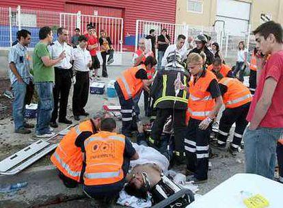 Asistentes sanitarios y bomberos atienden a dos de los heridos arrollados ante la discoteca Manhattan.