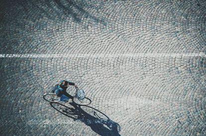 Una persona circula en bicicleta por la calle.