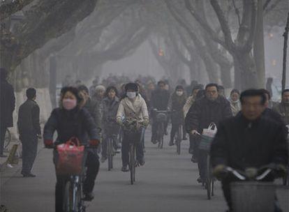 Ciclistas circulan con mascarillas por las calles de Nanjing.