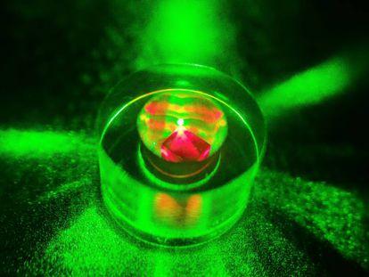 El diamante dentro del anillo de zafiro e iluminado por un rayo láser.