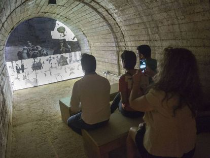 Visitantes del refugio de Castellón ante uno de los documentales que se proyectan en el interior.