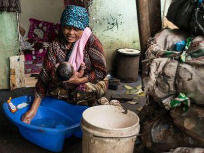Mak Muji es una recicladora de Yakarta que, cuando no recoge plástico en el vertedero, ejerce de comadrona