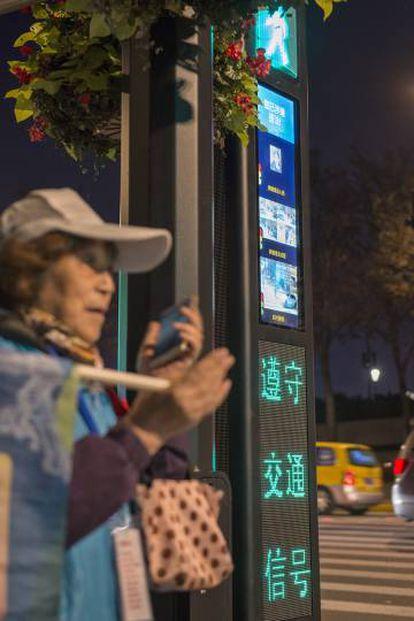 Una mujer asistente de tráfico junto a uno de los nuevos semáforos de reconocimiento facial.