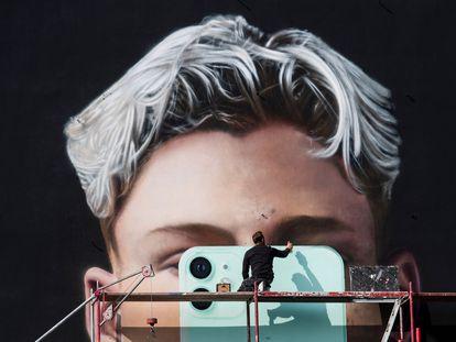 Un artista pinta un mural para el fabricante de teléfonos inteligentes Apple, en Berlín, en octubre de 2020.