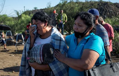 The relatives of the miners found dead wait at the gates of the mine in Coahuila.