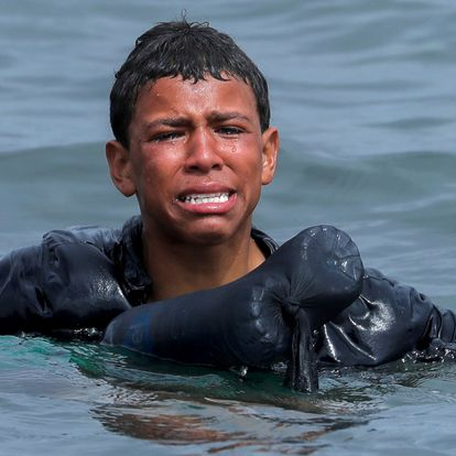 A Moroccan boy cries as he swims using bottles as a float, near the fence between the Spanish-Moroccan border, after thousands of migrants swam across the border, in Ceuta, Spain, May 19, 2021. Picture taken May 19, 2021. REUTERS/Jon Nazca