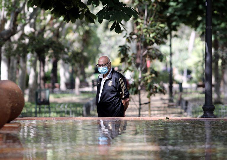 Un hombre con mascarilla pasea en el parque Calero de Madrid, una de las zonas verdes que el Ayuntamiento ha abierto este viernes.
