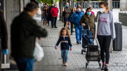 Una madre y su hija esperan en una cola para hacer la compra en Madrid, en una fila de personas protegidas con mascarillas frente al coronavirus.