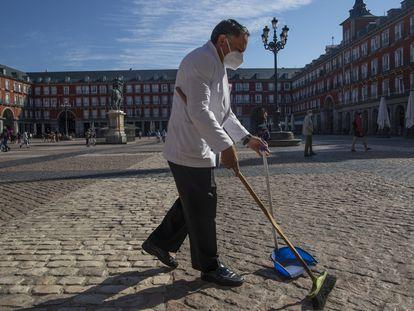 Un camarero barre antes de instalar la terraza en la plaza Mayor de Madrid, el pasado 9 de octubre.