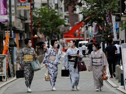 Unas mujeres pasean en Tokio con el traje tradicional de 'geisha', en julio.