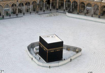Agentes de la policía vigilan la Kaaba, el gran cubo que se encuentra en la Gran Mezquita de La Meca, en Arabia Saudí, el pasado 6 de marzo. El lugar santo de los musulmanes se encontraba vacío en una medida para intentar luchar contra la epidemia del coronavirus.