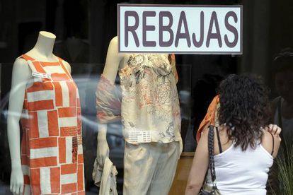 Una mujer mira un escaparate de una tienda en rebajas