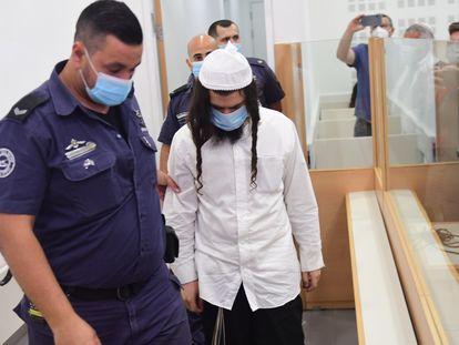 Amiram Ben Uliel es conducido por un agente, este lunes en el tribunal israelí de Lod.