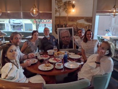 La familia de Juan José Fernández, comiendo en el Café Varela, uno de sus lugares predilectos, junto a su retrato el pasado mes de julio