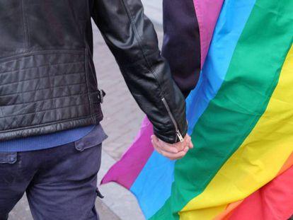 una pareja se coge la mano con la bandera multicolor, en una foto de archivo.