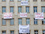 "FILE PHOTO: Banners hang from an apartment block on Karl Marx Allee in Berlin, Germany, November 20, 2018, to protest against plans to sell flats on a boulevard of imposing Stalinist architecture that was one of the flagship building projects of the former German Democratic Republic after World War Two. Banners read ""capitalist avenue"" and ""tenants action against speculation"". Picture taken November 20, 2018.     REUTERS/Joachim Herrmann/File Photo"