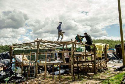 Los inmigrantes que esperan para cruzar el Canal construyen un refugio en la zona de Calais (Francia).