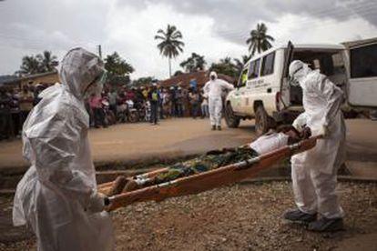 Dos enfermeros transportan a un enfermo de ébola en Sierra Leona.