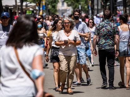 Varias personas pasean sin mascarilla por el centro de Madrid.