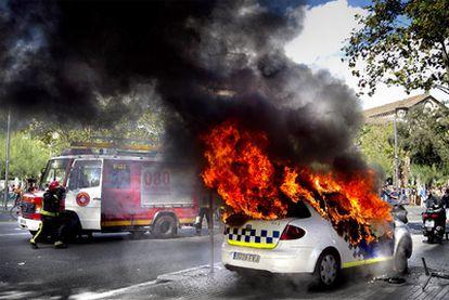 Un coche de la Guardia Urbana en llamas en los disturbios que se produjeron ayer al mediodía en el centro de Barcelona.