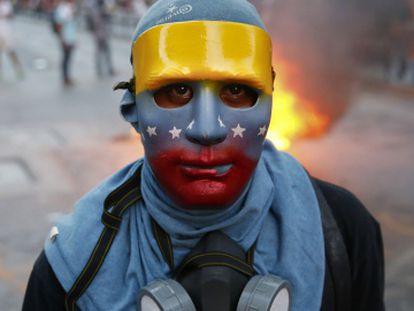 Un joven enmascarado participa en una protesta en Caracas.