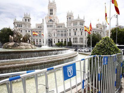 La fuente de la Cibeles, en Madrid, rodeada de vallas y banderas de España.