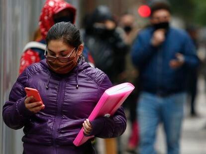 Una mujer consulta su teléfono móvil mientras anda por Santiago de Chile.
