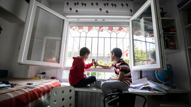 Dos niños  juegan en la ventana de su casa en Madrid, durante el confinamiento.