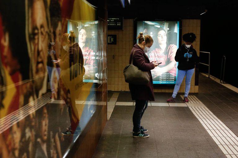 Dos mujeres miran el móvil en el metro de Barcelona.