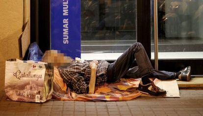 Un sin techo, durmiendo a la intemperie a las puertas de una oficina bancaria en Barcelona.