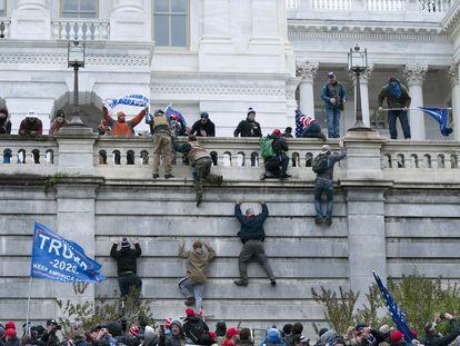 Partidarios de Donald Trump escalan la pared oeste del Capitolio de Estados Unidos, en Washington (EE UU).