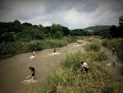 Un grupo de inmigrantes centroamericanos toman un baño en el río lagarteros de Chiapas.
