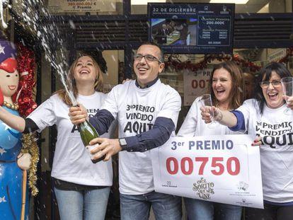 Los empleados de la Administración de Valencia que ha repartido el tercero premio de la lotería de Navidad, celebran la suerte.