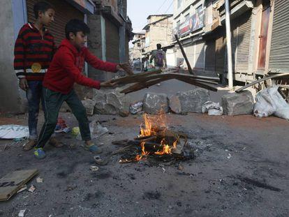 Niños intentan avivar un fuego cerca de una barricada en el centro de Srinagar, la principal ciudad del valle de Cachemira, este jueves.